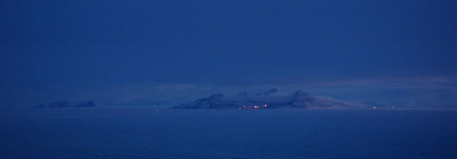 In the distance, across the sea ice and the ice shelf, are the lights of McMurdo station (center) and Scott Base (the New Zealand base, on the right). The photo is taken in very early September from Black Island, the main communications hub for the US Antarctic Program's McMurdo Station and South Pole Station.